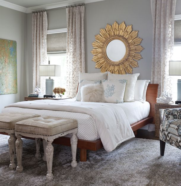 Large sunburst gold mirror on blue/gray wall with bed underneath and white bedding. Tufted footstools are in front of the bed.