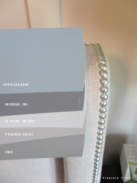 Side-by-side comparison of Behr Atmospheric, Behr Pier, Behr Fashion Gray, Behr Classic Silver, Behr Antique Tin next to an upholstered chair which makes the colors look more toned-down.
