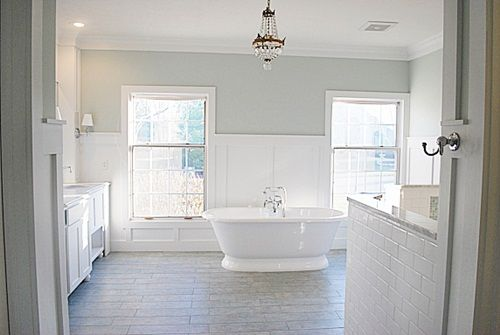 White bathroom with a hint of green on the walls and a chandelier above the stand alone bathtub.