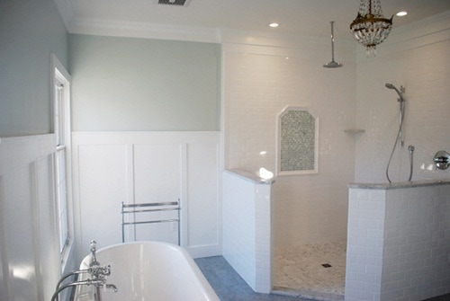 White bathroom with gray green walls and claw foot tub, and chandelier.
