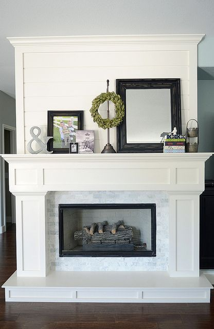 White fireplace with marble subways and shiplap trim.