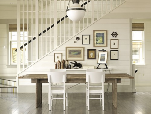 Cute gallery wall on shiplap leading up a staircase.