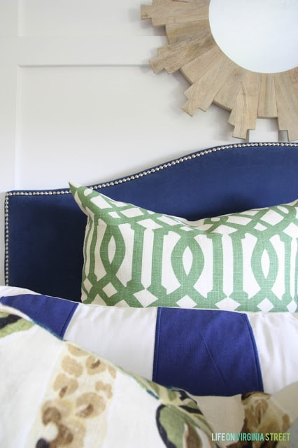 Blue headboard with blue, green and white bedding