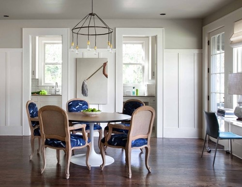 Dining room featuring white batten board with blue accents on the chair.