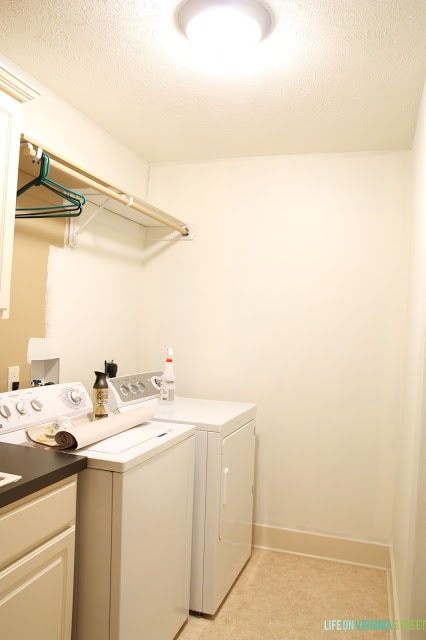 The white walls, washer and dryer, and brown countertops in laundry room.