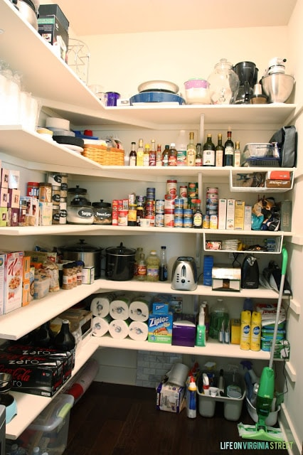 Organized pantry with food and mixing bowls and a swiffer.