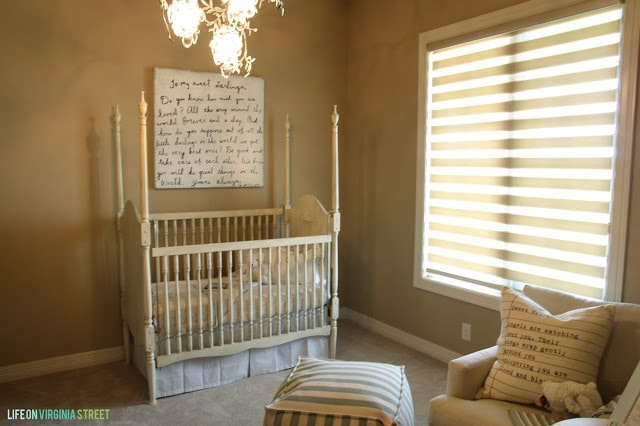 Nursery with Sugarboo Art, a Striped Pouf and French details.