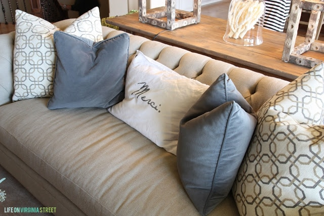 Tan couch with blue-gray and Merci pillows.