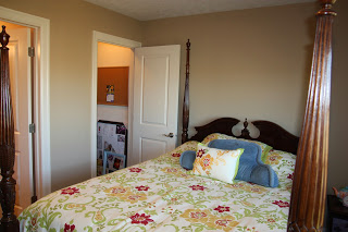A small room with a large four poster bed and floral bedspread on it.