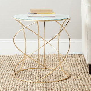 A gold and glass side table with books on it.