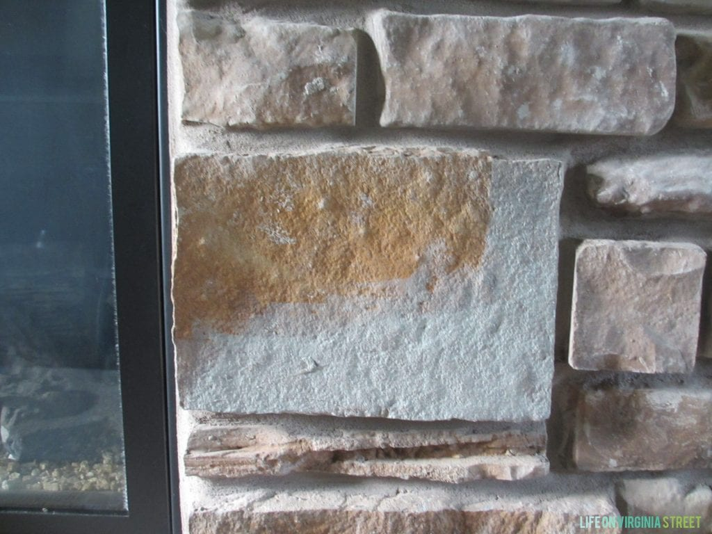 This gray-washed fireplace stone looks so much better now! Great tutorial with helpful tips on gray-washing your own stone or brick fireplace!