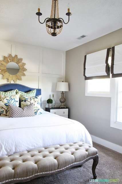Wooden chandelier, white bedspread, blue headboard and nightstand with a lamp in the guest bedroom.