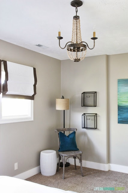 The corner of the guest bedroom with a wooden chair with a blue pillow on it, and a wooden chandelier above it.