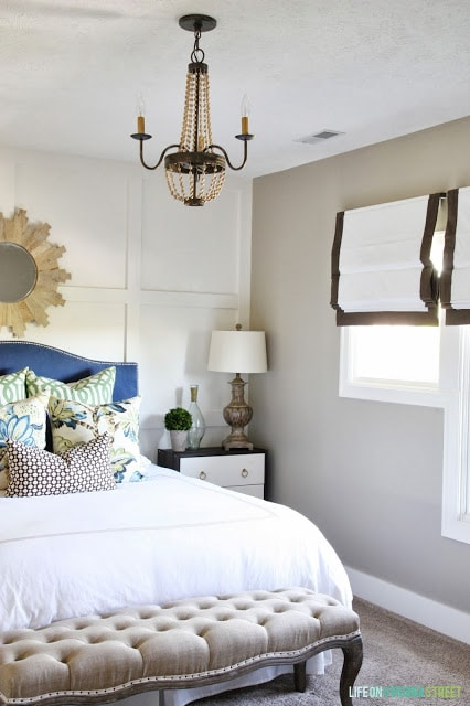Guest bedroom with a wood bead chandelier, blue headboard, white bedding, and a linen and oak bench.