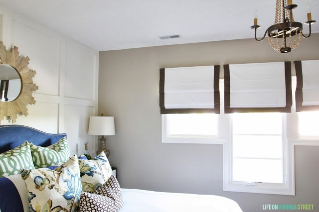 White and brown window shades half drawn, a bed with a blue headboard and a round mirror behind it on the wall.