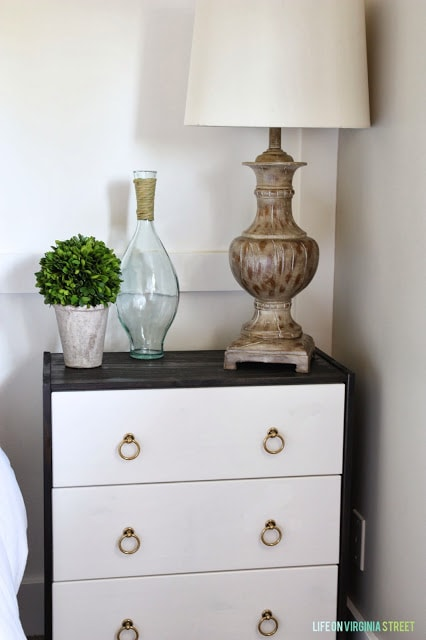 A nightstand with a ceramic lamp and white shade on it. A green topiary and clear glass vase.