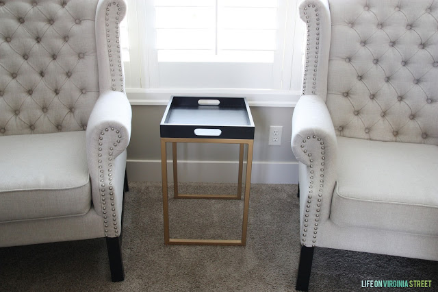 A gold legged side table with a black tray top.