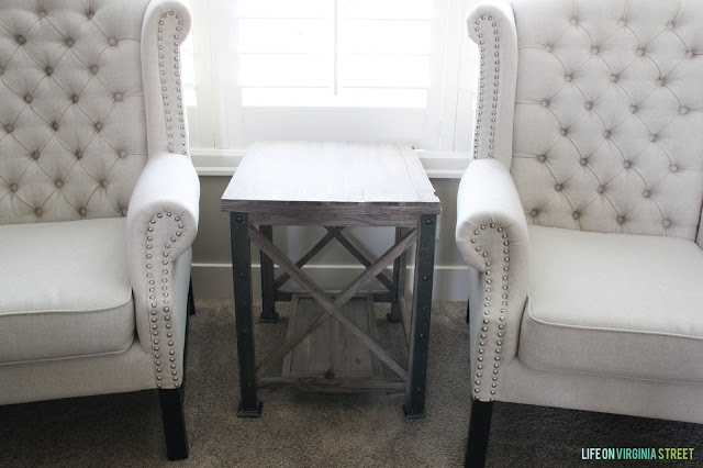 Two neutral pin tucked chairs with a wooden side table in between.