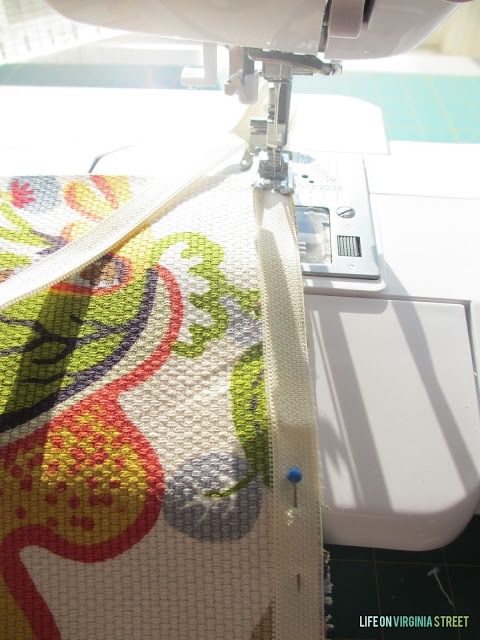 A sewing machine sewing the zipper in.