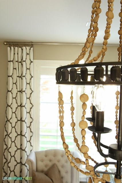 Side view of the chandelier with black and white curtains behind it.