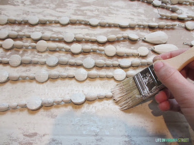 Painting the beads white with a paint brush.
