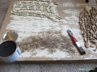 The beads on cardboard, a can of wax, a paint brush.