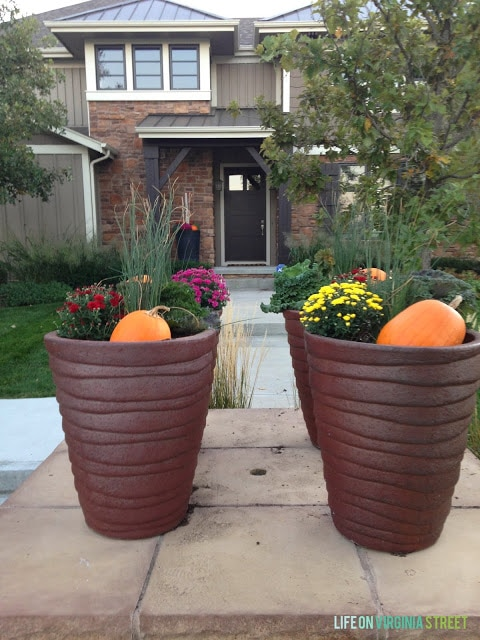 Large planter filled with flowers and pumpkins in front of house.