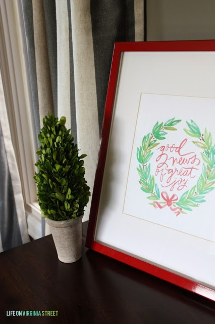 A printable framed and a topiary on the side table.