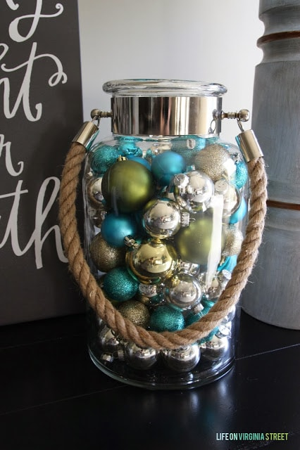 A clear glass jar filled with blue, green and silver ornaments.