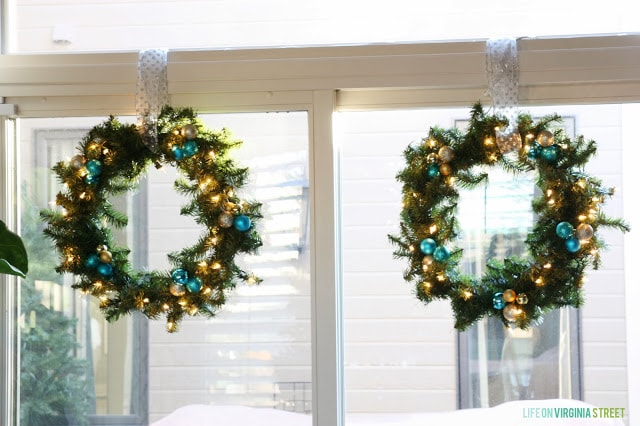 White window sill and blue and gold sparkly wreath hanging by ribbon.