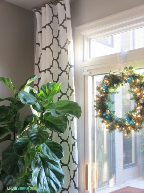 A green plant, black and white curtains and a wreath on the window.