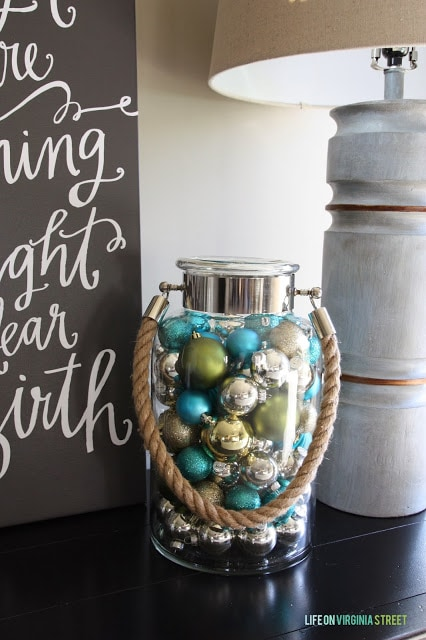 Multi colored ornaments in a glass jar with rope as a carrying handle.