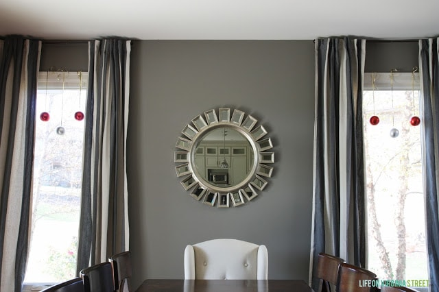 A round mirror in the dining room.