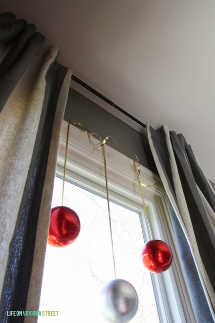 Red and silver ornaments hanging in the window.