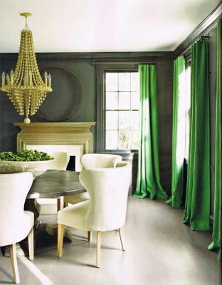 Emerald green curtains, and a wooden chandelier in dining room.