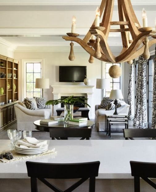 Wooden chunky chandelier above dining room table that is white with dark brown chairs.