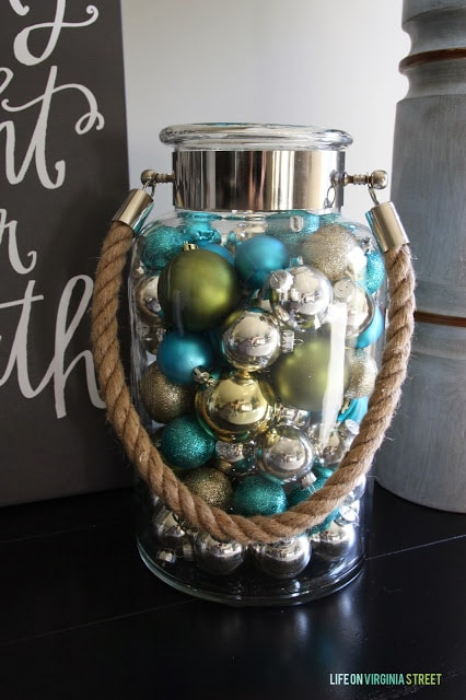 A clear glass jar is filled with Christmas ornaments in blue, green and silver.