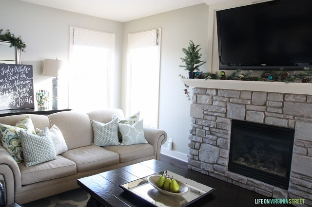 A living room that is neutral with sprigs of holly and ornaments on the mantel.