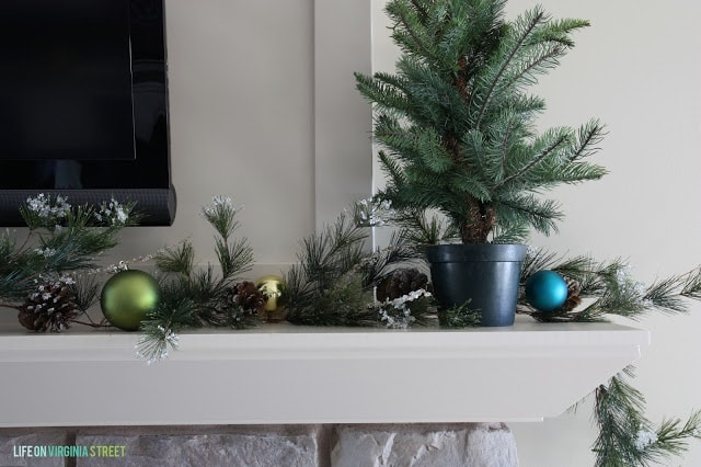 There is a small Christmas tree on the mantel.
