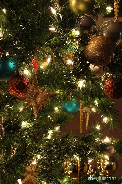 Blue and gold ornaments hang on the Christmas tree.