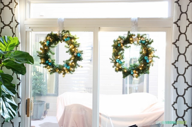 Two wreaths in blue and gold hang on the window.