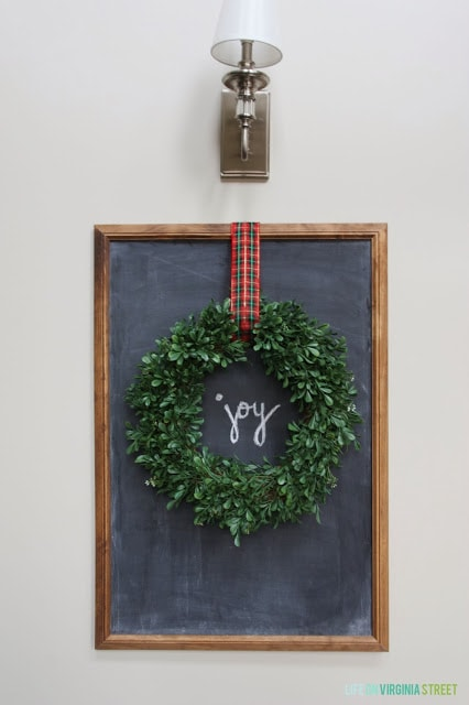A chalkboard with a wreath hanging on it by a plaid ribbon.