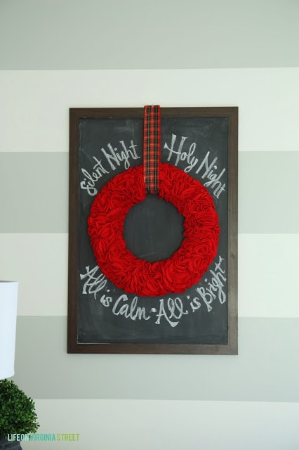 A red ruffle wreath hangs on the wall in the bedroom.