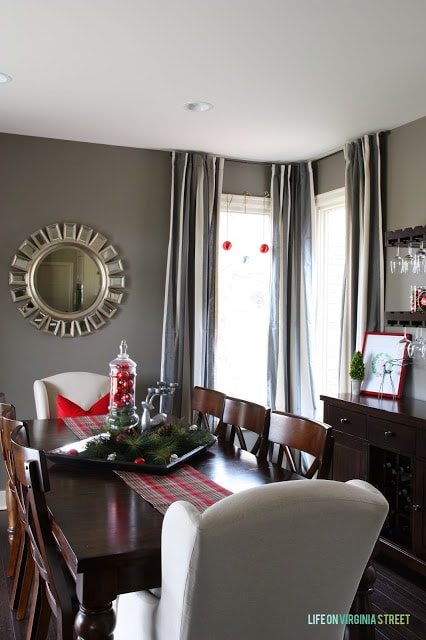 A dining room with a wooden table and a starburst mirror at the head of the table on the wall.