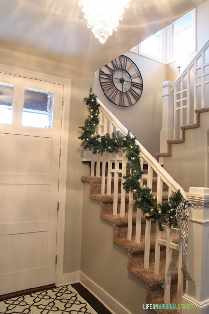The stairs in the entryway with garland on the railing.