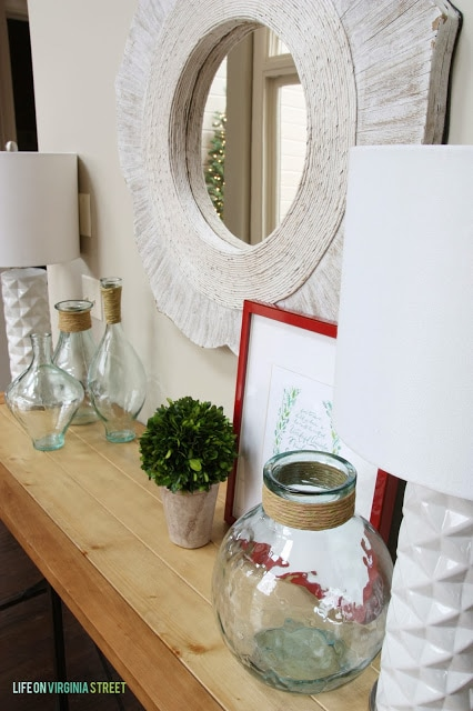 There is a white mirror above a wooden console table filled with clear glass.
