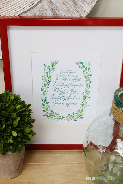 A red picture frame has a Christmas quote inside it.