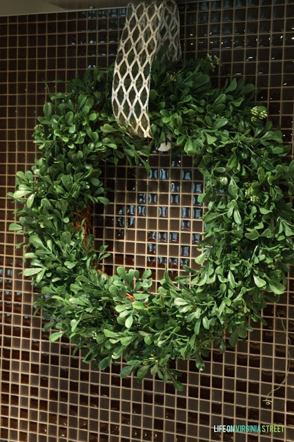 The wreath hangs in the kitchen by a ribbon.