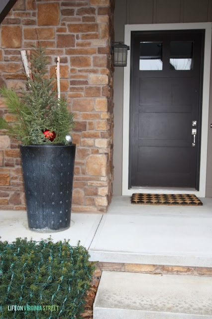 There is a planter on the front porch with a Christmas tree in it decorated with ornaments.