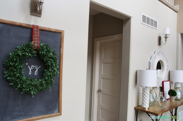 There is a chalkboard in the entryway with a wreath on it and the word joy written on the chalkboard.